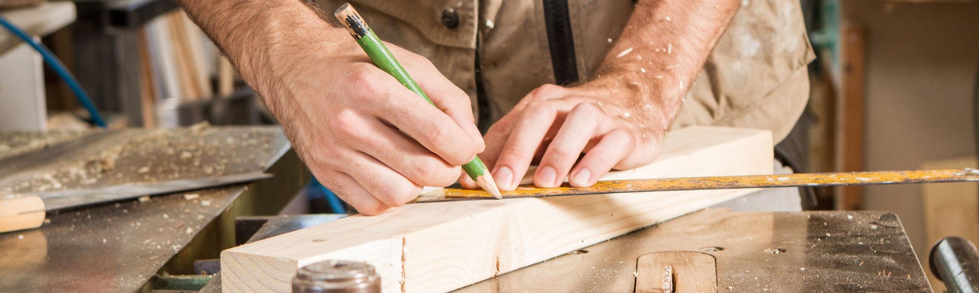 Schreiner der etwas auf einem Holz anzeichnet